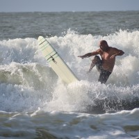 Surfer kicks the Board hard in the rough Surf on 8/8/2017.