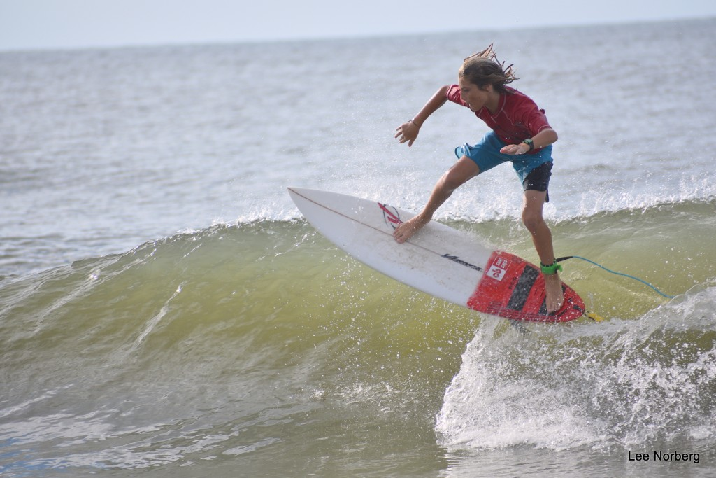 Young Lady Surfer kick down hard on the Board while