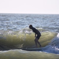 Long Board Surfer Scott Nixon rides out a Wave at The