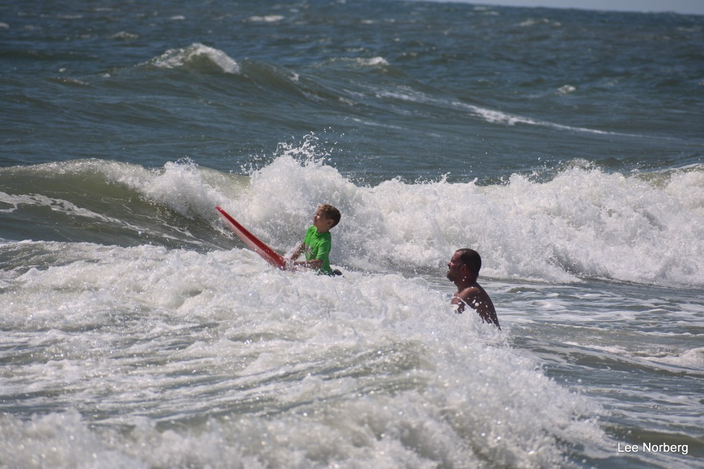 Young Surfer gets an assist from his Dad to clear a