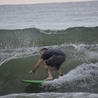 Surfer walks the nose of the Board to catch the curl