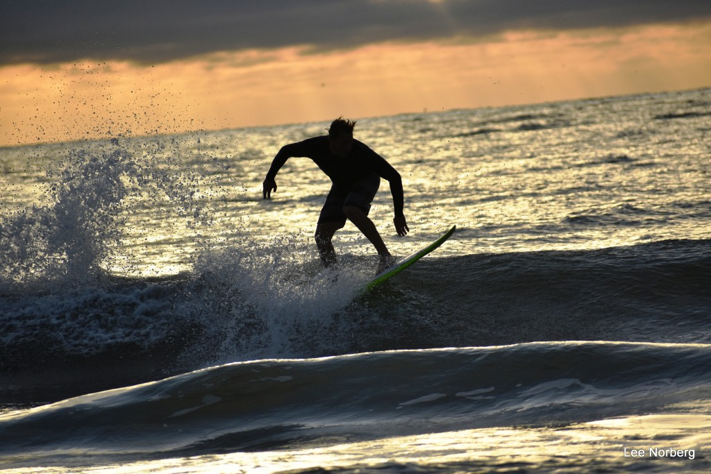 Surfer Hal Stalnaker works a Wave at Sunrise in silhouette.